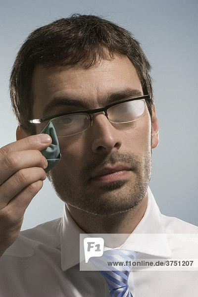 Geschäftsmann putzt sich beschlagene Brille