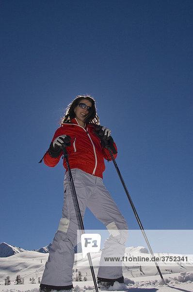 Junge Frau auf Ski  posiert gegen Sonne und blauem Himmel vor Bergkulisse