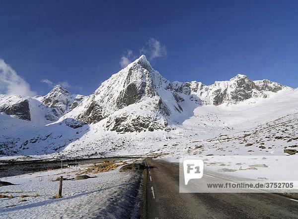 Straße vor gebirgiger Winterlandschaft auf den Lofoten  Norwegen  Skandinavien