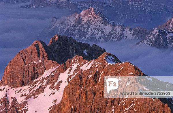 View from the summit of Mount Zugspitze  mountain peaks bathed in pink evening light  Bavaria  Germany  Europe