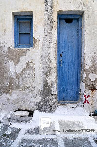 Schmale alte Holztüre mit verwitterter blauer Farbe in einer Gasse mit Steinboden in Naxos  Kykladen  Griechenland  Europa