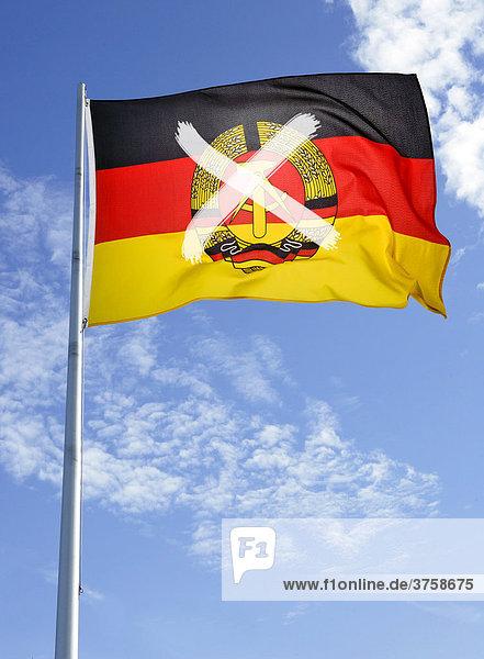 DDR-Fahne am Mast vor Wolkenhimmel  durchgestrichen mit einem Kreuz