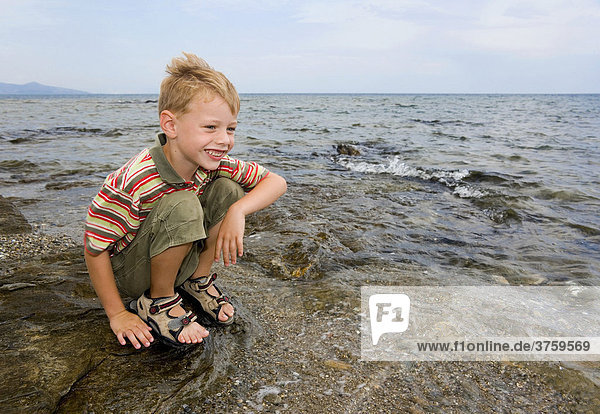 A five-year-old boy is playing at the Mediterranean Sea by St Lucia  Sardinia  Italy  Europe