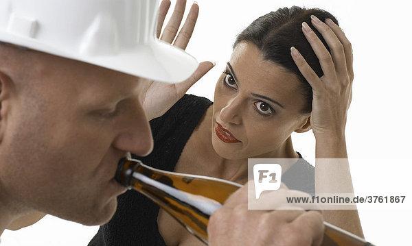 Ein Arbeiter drinkt Bier  Frau ist genervt