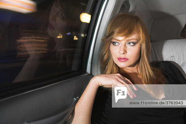 Woman in a stretched limousine at night
