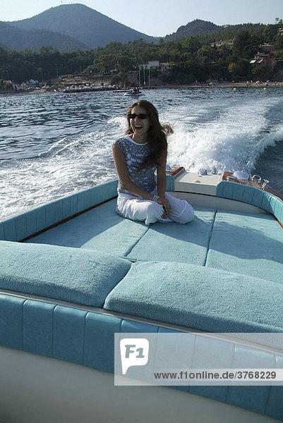 Junge Frau auf der Liegefläche eines Riva Motorboots bei voller Fahrt  ThÈoule-sur-Mer  Frankreich  Europa