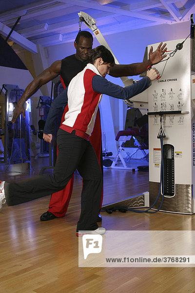 Personal trainer coaching young woman with cable machine at a gym