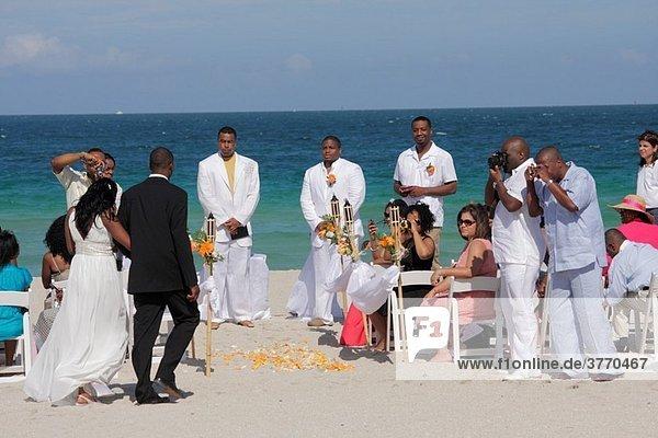 Florida  Miami Beach  Atlantic Ocean  public beach  seashore  destination wedding  ceremony  Black  man  woman  couple  guest  groom  bride  marriage  celebration  white dress  taking photo  flower petals
