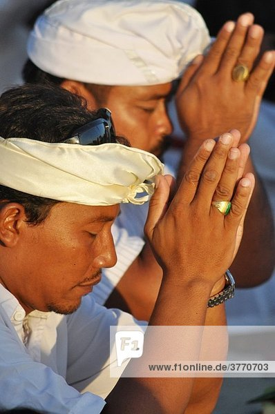 Kuta Beach (Bali  Indonesia): man at a collective pray during a Hindu ritual on the beach