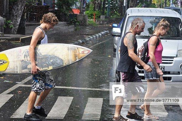 Legian (Bali  Indonesia): Australian tourists crossing a street under the rain Legian (Bali, Indonesia): Australian tourists crossing a street under the rain