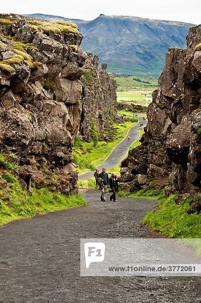 Tourist walking across Pingvellir National Park Iceland
