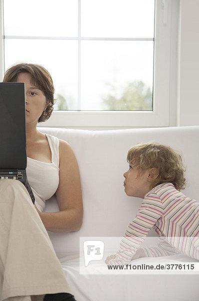 Mutter am Computer neben dem Kind