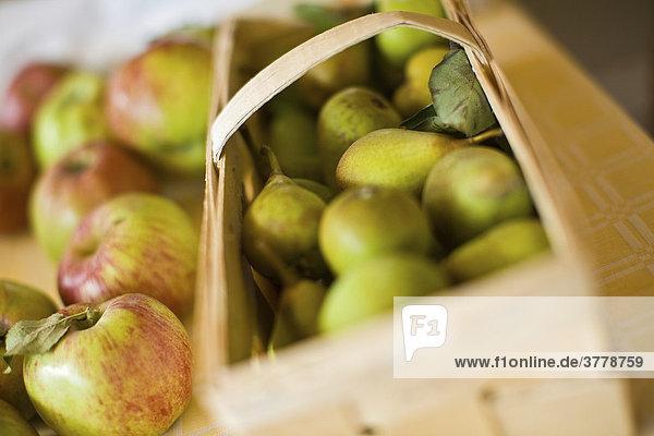 Äpfel neben Birnenkorb