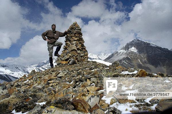 Bergsteiger an Steinhaufen auf 5237 m hohem Gipfel mit etwas Schnee Phu Nar-Phu Annapurna Region Nepal