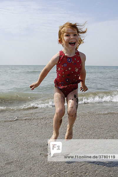 Child hops at the beach in the sea surf
