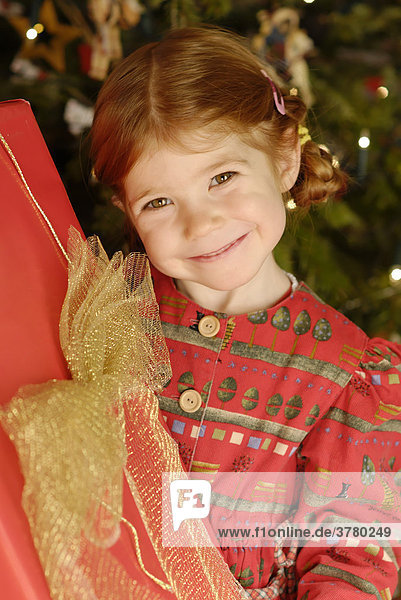 Child is happy with a christmas present under the christmas tree