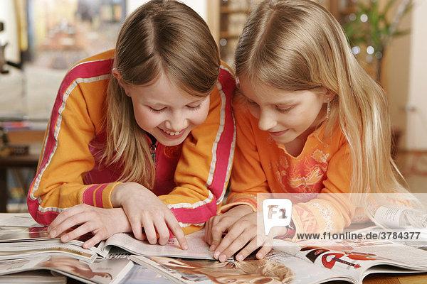 2 Mädchen lesen in Zeitschriften