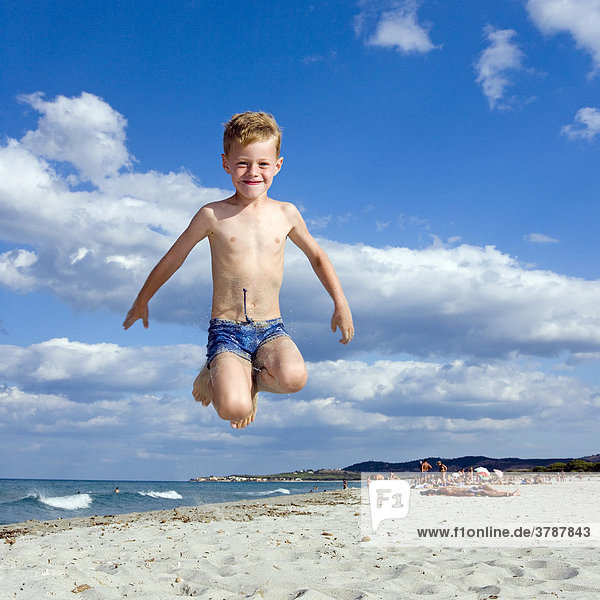 A boy  five years old  does a caper on the beach of La Caletta  Sardinia  Italy