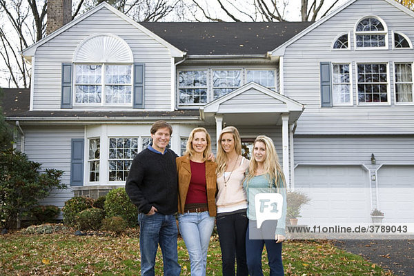 Eine vierköpfige Familie  die vor ihrem Haus steht.