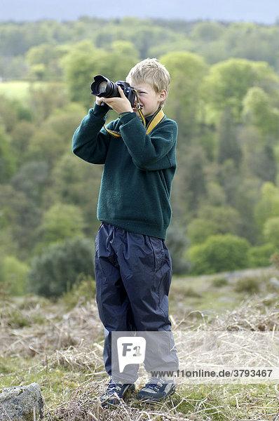 Boy taking pictures Dartmoor National Park Devon England