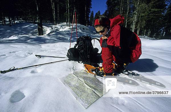 Frau studiert die Landkarte bei einer Schneeschuh-Wanderung im Karwendel Deutschland