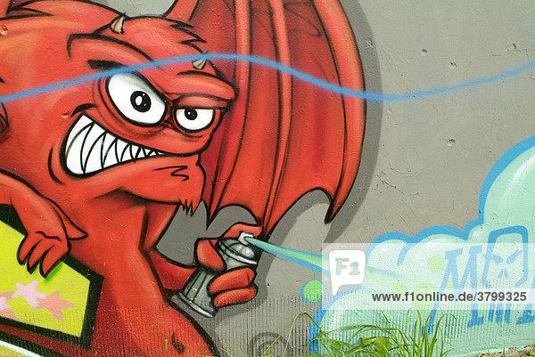Auf der Rueckseite einer Garagenanalage tobt sich ein Teil der Berliner Graffitiszene aus. Roter Teufel sprueht mit verzerrtem Gesicht. Hier ein Auf der Rueckseite einer Garagenanalage tobt sich ein Teil der Berliner Graffitiszene aus. Roter Teufel sprueht mit verzerrtem Gesicht. Hier ein