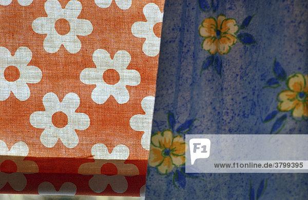 Besuch im Elterhaus: Details und Erinnerungen. Blaue Gardine mit Bluetenmuster am Fenster  Orangefarbenes Rollo mit Blumenmuster.