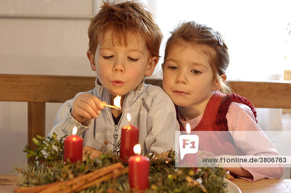 Children in the christmas time with candles and advent wreath