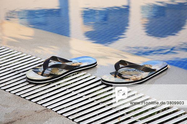 Badeschuhe am Rand eines Pools