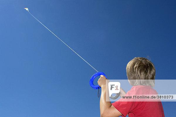 Junge lässt einen Lenkdrachen hoch am Himmel fliegen