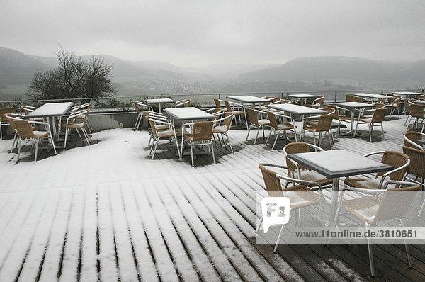 Gasthausterrasse mit verschneiten Tischen und Stühlen