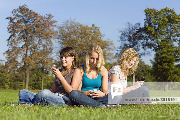 Two young women listen together to the music from a MP3-Player