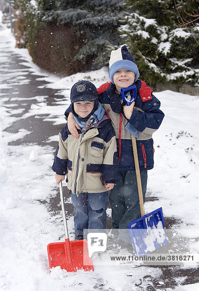 Two little boys with snow shovels