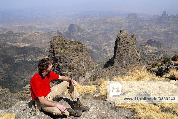 Bergsteiger genießt den Ausblick über weite Canyons und Berglandschaft von Imet Gogo (3926m) im Semien Mountains Nationalpark bei Geech Äthiopien