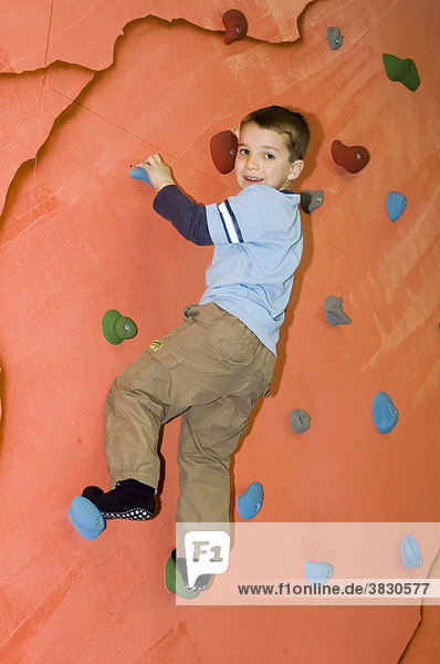 Children playing in an indoor playground at a climbing wall
