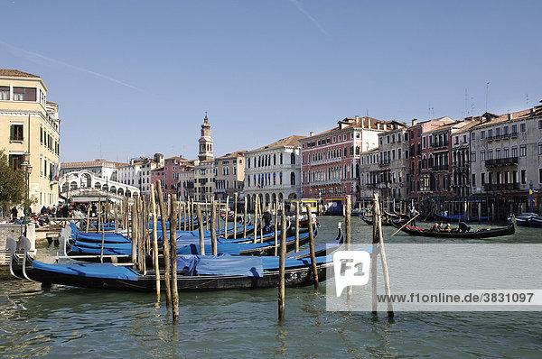 Blau zugedeckte Gondeln am Canale Grande mit Rialto Brücke im Hintergrund in Venedig Italien