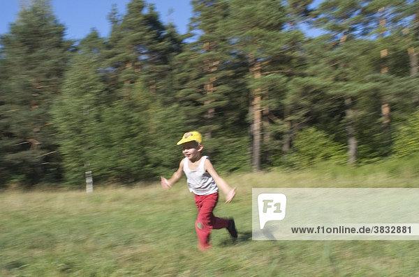 Sechs 6 Jahre alter Junge läuft mit ausgebreiteten Armen im Perlacher Forst in München Bayern Deutschland