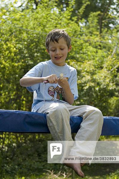 Achtjähriger Junge sitzt im Garten und schnitzt |