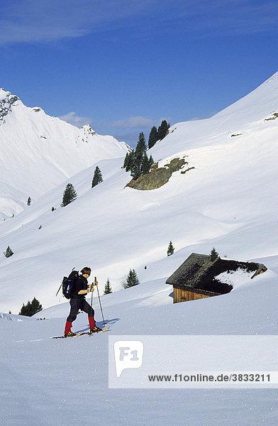 Schneeschuhgeherin an einer Hütte im Kleinwalsertal Österreich