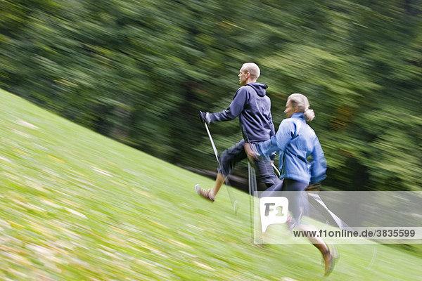 Zwei Nordic Walker mit Stöcke und sportliche Kleidung bergauf laufend auf einer grünen Wiese im Englichen Garten in München