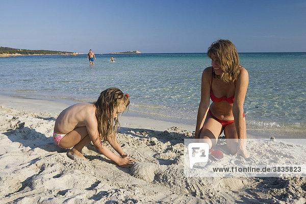 Mutter und Tochter am Strand beim Sandspielen  Cala Brandinchi  Sardinien  Italien