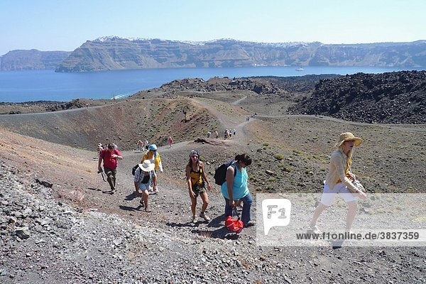 Tourists on Nea Kameni  the Active Island Volcano in the Caldera  Santorini  Cyclades Islands  Greece.