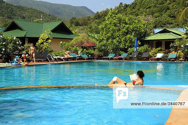 Frau liest im Swimmingpool  Ko Phangan  Thailand  Asien