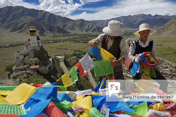 Tibetische Frauen mit Gebetsfahnen  Blick auf Yumbulagang Festung und Yarlung-Tal  Tsetang  Tibet  China  Asien