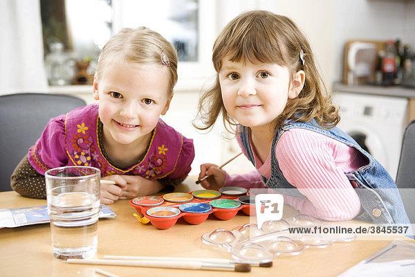 Zwei Mädchen malen mit Wasserfarben