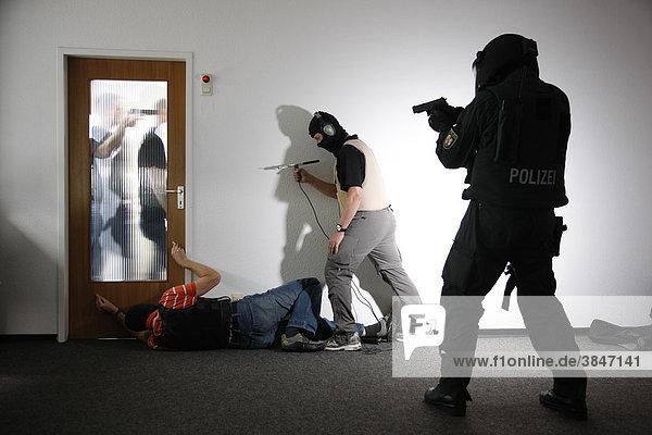 Mitglieder einer technischen Einsatzgruppe der polizeilichen Spezialeinheiten hören Gespräche hinter einer Tür  bei einer Geiselnahme  ab  gesichert von einem SEK Polizisten  Einsatzübung  Nordrhein-Westfalen  Deutschland  Europa