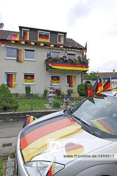Mit deutschen Flaggen geschmücktes Wohnhaus und Auto während Fußball WM 2010  Stuttgart  Baden-Württemberg  Deutschland  Europa