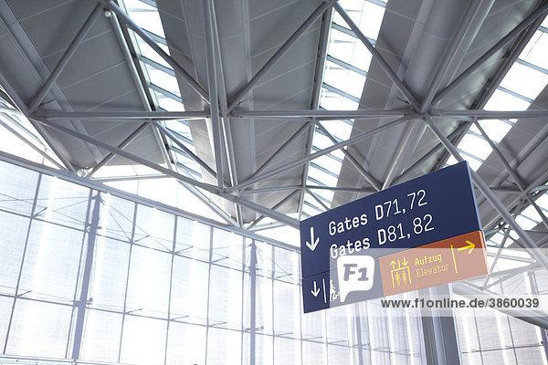 Hinweisschild auf Flughafen mit moderner Glasfassade