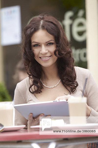 Junge Frau mit ebook Lesegerät iPad in Straßencafe