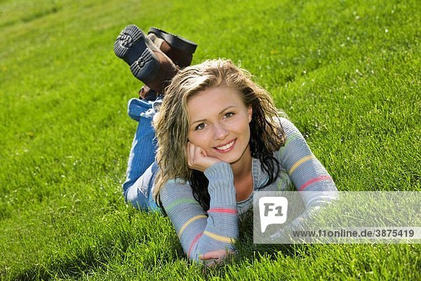 Caucasion teenage girl laying in the grass and smiling